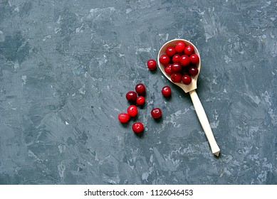 Ripe juicy cherry in wooden spoons on a dark gray concrete background. Copy space. Summer concept