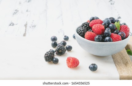 Ripe and juicy fresh berries in the bowl and on the marble wooden board over white rustic wooden backgrounds. Blueberry, Raspberry and Blackberry. Side view. Selective focus.