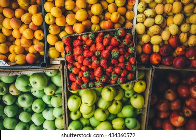 ripe juicy fruits and berries are in cardboard boxes summer day on the market. top view