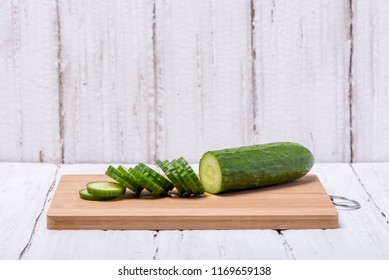 Ripe juicy green cucumber cut in circles on a wooden board on a white background