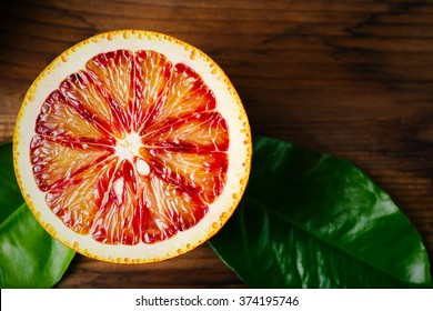 Ripe Juicy Half of an Orange Citrus Fruit Close Up on Wooden background. Vibrant Colors.