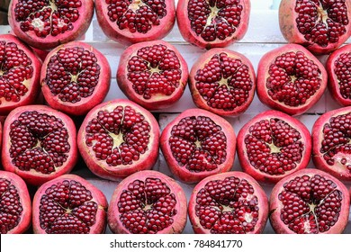 Ripe and juicy half peeled pomegranates ready to be squeezed for fresh juice on the winter market in Tel Aviv, Israel. Close up view