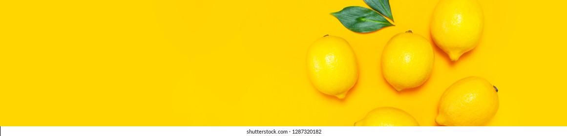 Ripe juicy lemons and green leaves on bright yellow background. Lemon fruit, citrus minimal concept, vitamin C. Creative summer food minimalistic background. Flat lay, top view, copy space Long banner