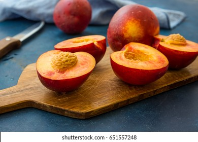 Ripe juicy nectarines, whole and halved on wood cutting board, knife, blue kitchen towel, close up, modern minimalist style