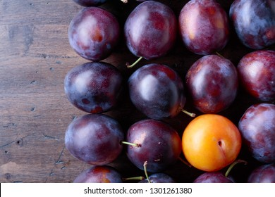 Ripe juicy plums on a wooden background. Top view, copy space.
