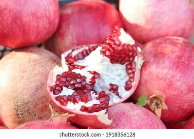 Ripe juicy pomegranate fruits close up. Organic fruits havesting. Cultivation of pomegranate fruits.
