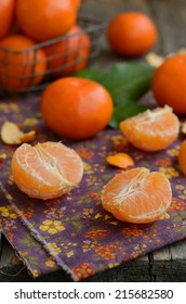 Ripe and juicy tangerine cloves over bright violet table napkin