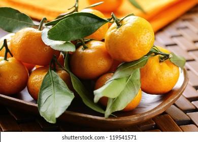 ripe juicy tangerine, orange mandarin  with leaves on  wooden table