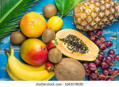 Ripe Juicy Tropical Summer Seasonal Fruits Mango Papaya Pineapple Coconut Kiwi Bananas Strawberries Grapes Citrus on Large Palm Leaf on Blue Wood Background. Vacation Healthy Lifestyle Superfoods