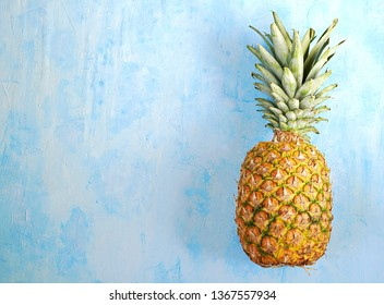 Ripe and juicy whole pineapple on a light blue concrete background. Tropical fruit. Summer concept. Top view, copy space.