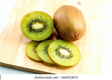 The ripe kiwi fruit and the half-fruit are placed on the wood.