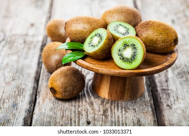 Ripe kiwi in a wooden dish on a wooden background. Healthy eating.