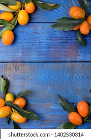 Ripe kumquats with leaves are framing copy space on blue wooden table