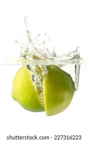Ripe lime falling into water, splashes all around.