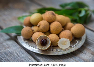 Ripe longan on an old wooden background. Exotic fruit, selective soft focus