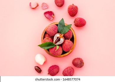 Ripe lychee. Exotic asian fruits in bowl on pink desk top-down copy space