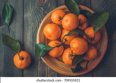 Ripe mandarine with leaves, tangerine mandarine orange on wooden table background. Citrus fruits Mandarins in plate. Top view, copy space, toning image