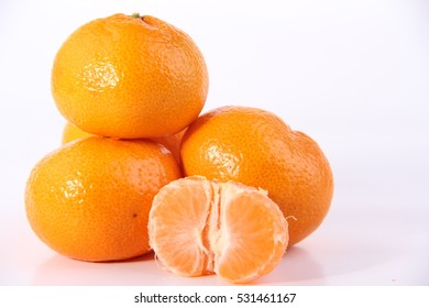 Ripe mandarines with leaves close-up on a white background.