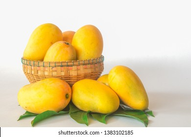 Ripe mangos in a basket on a white background