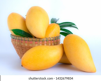 ripe mangos and leaves in a basket on a white background