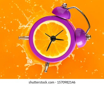 Ripe orange in alarm clock on color background with splashes