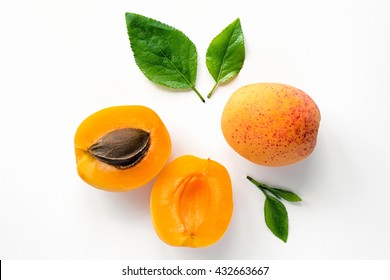 Ripe orange apricots with leaves on white background. Isolated fruit.