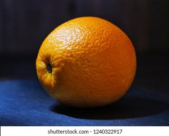 Ripe orange on dark background, macro