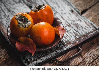 Ripe orange persimmon fruit and persimmon leaves in a brown plate on a brown wooden table. fresh fruits