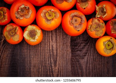 Ripe orange persimmon fruit on brown wooden table. Organic persimmon fruit  at market. Persimmons background with copy space, text place