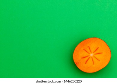 Ripe orange persimmon fruit on green table. Persimmon fruit cut in half,  top view, copy space