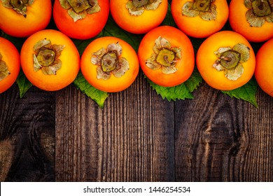 Ripe orange persimmon fruit on brown wooden table. Persimmons background with copy space, text place