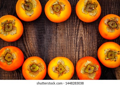 Ripe orange sharon fruit on brown wooden table. Persimmons background with copy space, text place
