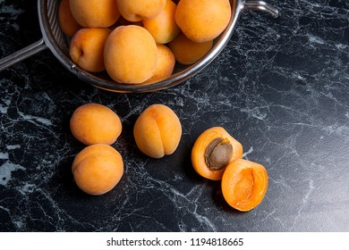 Ripe organic apricots in steel colander. Composition in rustic style - organic yellow juicy apricots in steel colander and whole and halved apricots on dark marble background. Harvest time.