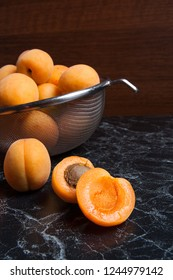 Ripe organic apricots in steel colander. Composition in rustic style - organic yellow juicy apricots in steel colander and whole and halved apricots on dark marble background. Healthy food concept.