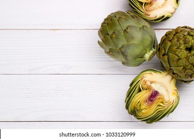 Ripe organic artichokes on white wooden table, copy space