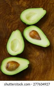 ripe organic avocado cut in half on a wooden  background