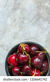 Ripe Organic Freshly Picked Wet Sweet Cherries in Vintage Enamel Mug on Grey Metal Stone Concrete Background. Garden Table. Flat Lay. Summer Harvest Vitamins Clean Eating Freshness Vegan