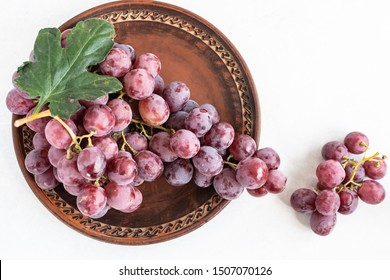 Ripe organic red grape on the dark clay plate top view. Autumn harvest concept. Tasty and healthy dessert concept.