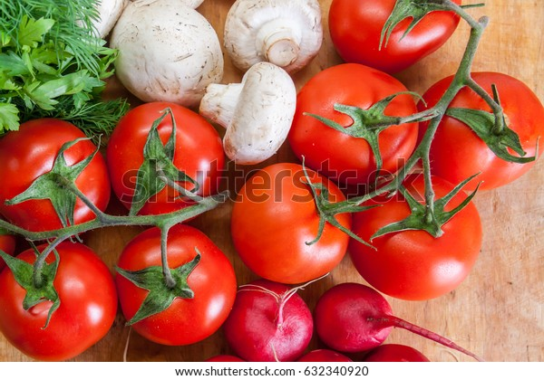 Ripe organic tomatoes, mushrooms and greens on a wooden background