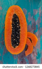 Ripe papaya with slices on turquoise wooden background from above. Healthy fruit eating.