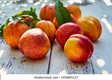 Ripe peaches with leaves on the old wooden table against the background of green leaves in the garden. Soft selective focus
