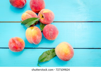 Ripe peaches with leaves on rustic blue wooden table. Top view. Flat lay.