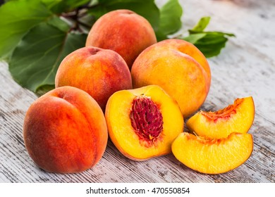 Ripe peaches and leaves on table