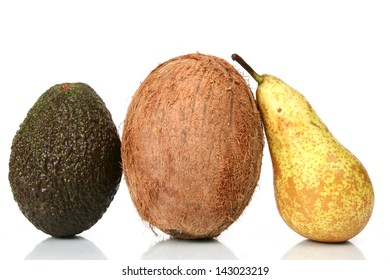 A ripe pear, avocado and a coconut on white background with a soft reflection.