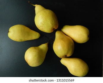 Ripe pears on black background as a low-calorie source of folic and organic acids, pectin, carotene, vitamins C, B1, P, PP, flavonoids. Healthy food concept.