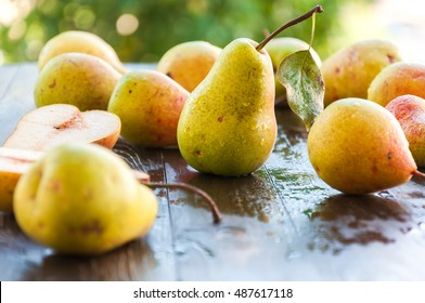 Ripe pears on rustic wooden table in the garden, nature after rain, organic fruit harvest. Harvest pears.