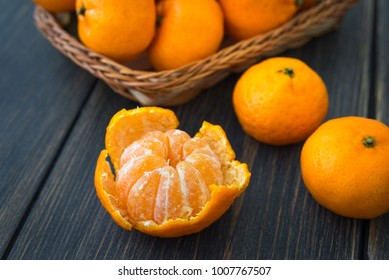 Ripe peeled tangerine and a wicker basket of juicy orange clementines or Algerian mandarins on black wooden background close-up