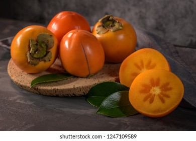 Ripe persimmon fruits in a cork plate on dark kitchen counter top.