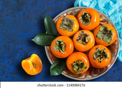 Ripe persimmon on metal plate with blue gauze napkin on textured background. Persimmon is source of vitamin C, iodine, iron, potassium and magnesium. Useful for prevention of cardiovascular disease