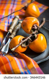 Ripe persimmons fruits on rustic background